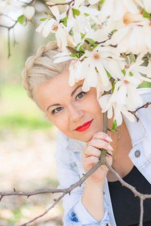 Beata Majewska trzyma gałąź z białymi kwiatami