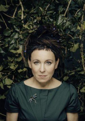 Olga Tokarczuk w zielonej sukience, w tle liście