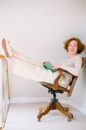 Diane Setterfield na kręconym krześle z nogami w górze i książką w ręku