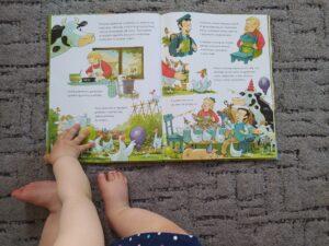 Krowa Matylda obchodzi urodziny otwarta książka Widać nóżki i rączkę dziecka przewracającego stronę
