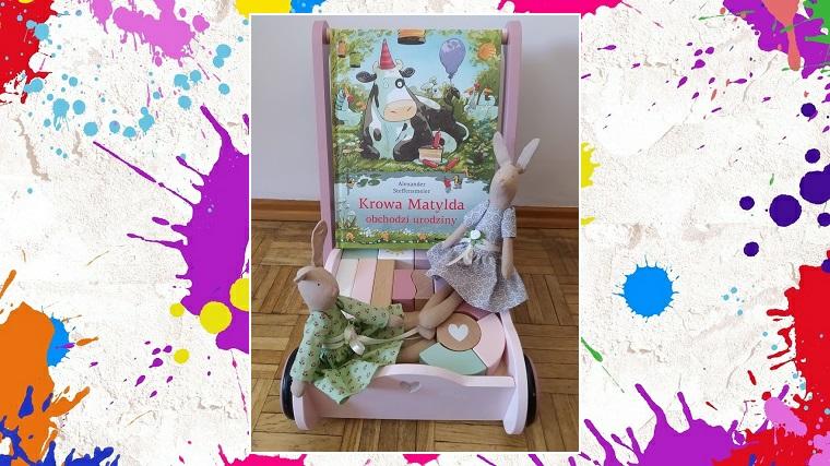 Krowa Matylda obchodzi urodziny zdjęcie główne książka ustawiona na wózku z klockami i dwoma ręcznie robionymi królikami szmaciankami