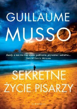 """""""Sekretne życie pisarzy"""", Guillaume Musso, okładka, samotna postać na pięknej plaży, w oddali klify"""